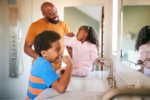 Parent teaching children to brush their teeth properly.
